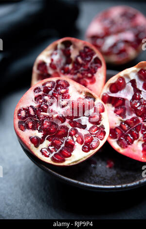 Ripe cut pomegranate on a slate plate. Red and dark colors composition Stock Photo