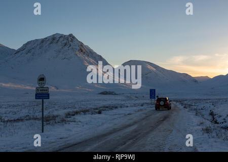 Car on the Glen Etive road during difficult winter driving conditions. Late afternoon, Glen Etive, Highland, Scotland - Stock Photo