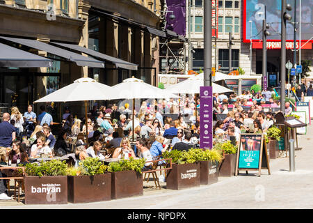 A summer day in Manchester city centre with many people sat eating and drinking outside Banyan Bar and other restaurants and bars of The Triangle, for - Stock Photo