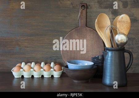 Crockery, clayware, dark utensils and other different stuff on wooden tabletop. Kitchen still life. - Stock Photo