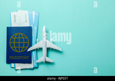 Tickets for plane and passport with model of passenger plane on green mint background. Copy space for text - Stock Photo