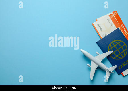 Tickets for plane and passport with model of passenger plane on blue background. Copy space for text. - Stock Photo