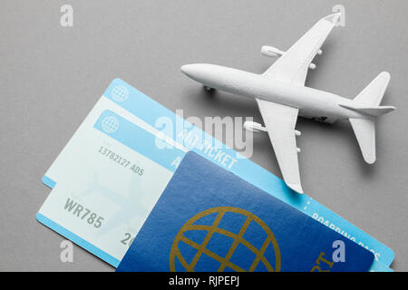 Tickets for plane and passport with model of passenger plane on gray background - Stock Photo