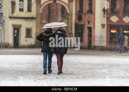 A couple walks in snow carrying an umbrella, Wrocław, Wroclaw, Wroklaw, Poland - Stock Photo