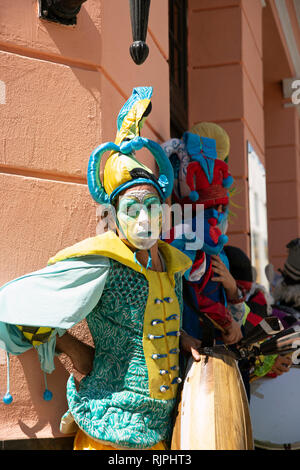 Two street theatre musicians with painted faces and wild circus costumes entertain on the streets of Havana Vieja Cuba - Stock Photo