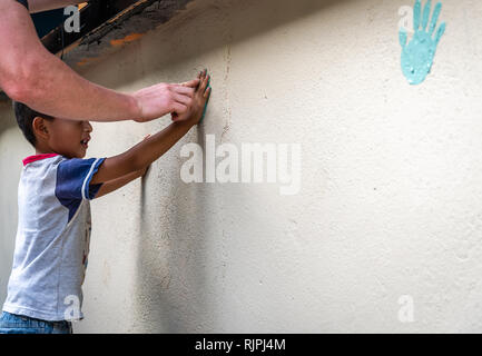 young latin boy making hand prints on wall in Guatemala - Stock Photo