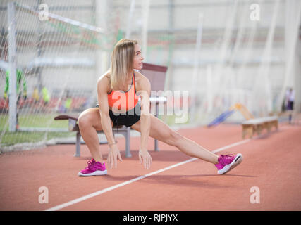 Young fit athletic woman stretching and preparing to run - Stock Photo