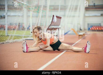 Young athletic woman stretching and preparing to run - Stock Photo