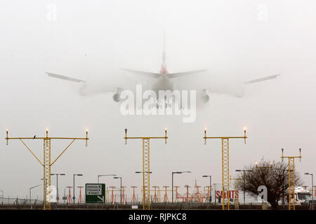 An aircraft lands at London Heathrow airport in heavy fog on March 13, 2014. - Stock Photo