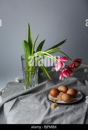 Boiled brown eggs on a plate next to the tulips in a transparent glass cup on a gray background in a muffled light and in soft focus - Stock Photo