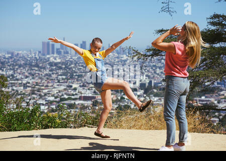 Two young female friends having fun on cityscape hilltop, Los Angeles, California, USA - Stock Photo