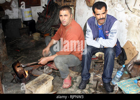Metalworkers in their workshop at the Place el Seffarine, Medina of Fes el Bali, Fez, Morocco - Stock Photo