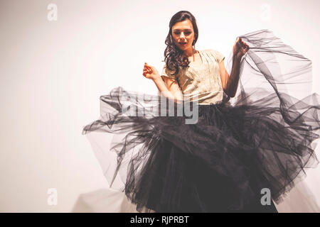 Woman holding tulle skirt dancing - Stock Photo