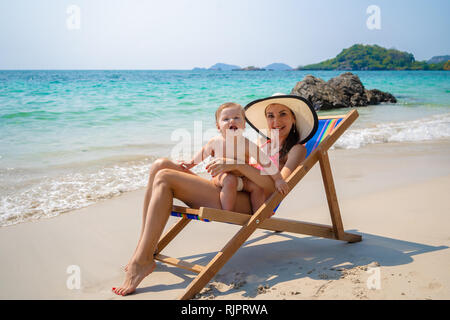Young mother and baby daughter on a lounger by the sea, a child plays, mother works on a laptop. Mom is a freelancer. Young mom business. Close up slow motion - Stock Photo