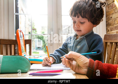 Mother and son writing in notebook - Stock Photo