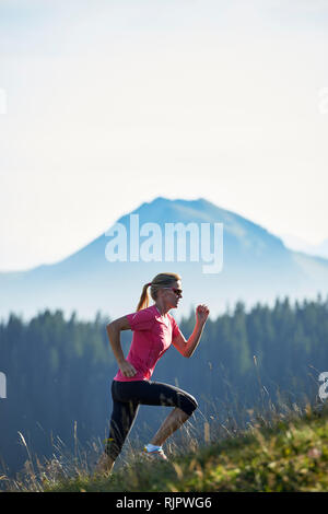 Jogger running up hillside, Manigod, Rhone-Alpes, France - Stock Photo