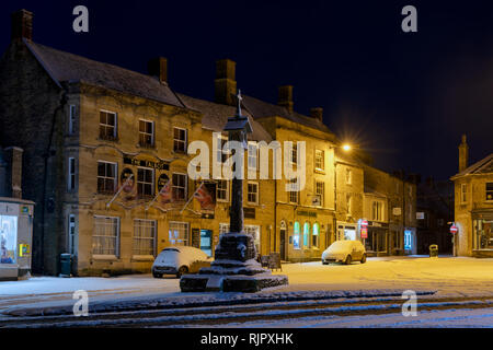 The Market Square Cross before dawn in the winter snow. Stow on the Wold, Cotswolds, Gloucestershire, England - Stock Photo