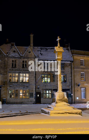 The Market Square Cross in front of the Kings Arms pub before dawn in the winter snow. Stow on the Wold, Cotswolds, Gloucestershire, England - Stock Photo