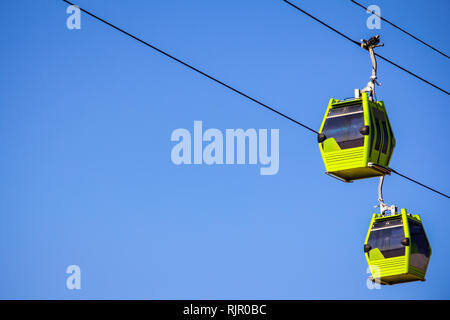 Funicular on the line isolated in blue sky with sun shining on the side - Stock Photo