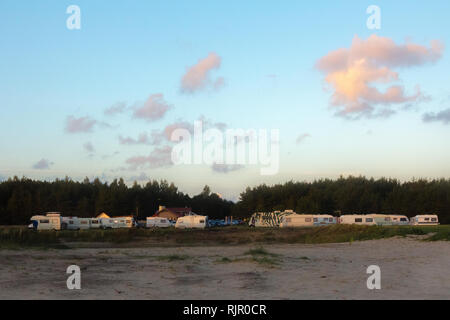 Scenic view of a caravan or trailer park next to woods in summer sunset with blue sky - Stock Photo