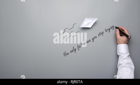 Conceptual image with origami paper boat and male hand writing an inspirational quote You only fail when you stop trying over grey background with cop - Stock Photo