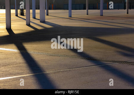 Modern architecture shadows on the ground back lit by warm evening sun. Sunset shadow - Stock Photo