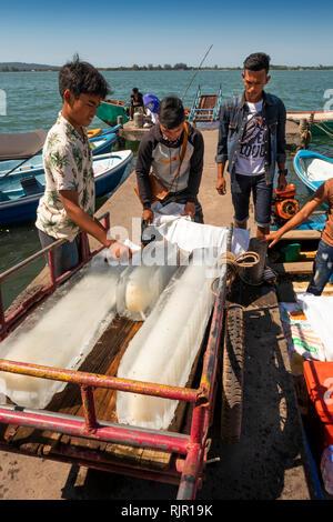 Cambodia, Preah Koh Kong, Prek Kaoh Pao river, Dong Tung Port jetty, man loading cut blocks of ice into sack