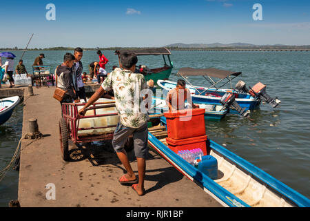Cambodia, Preah Koh Kong, Prek Kaoh Pao river, Dong Tung Port jetty, man with blocks of ice on trolley loading boat