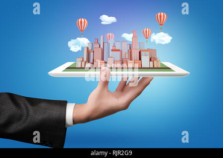 Businessman hand holding a tablet with city skyscrapers model, clouds and air balloons on blue background - Stock Photo