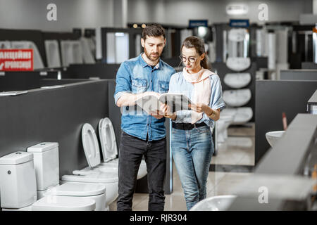 Young couple choosing lavatory pan standing together in the building shop with sanitary ceramics - Stock Photo