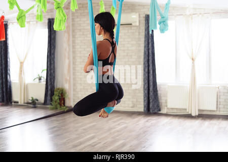 Full length of fit young woman doing antigravity yoga exercises in studio. Namaste butterfly pose. Side back view. - Stock Photo