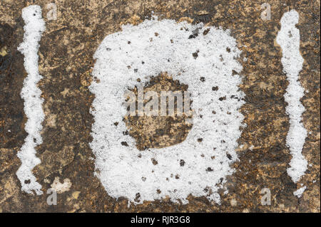 The police non-emergency number as seen on paving slabs and in snow a possible warning for motorists and the driving conditions - Stock Photo