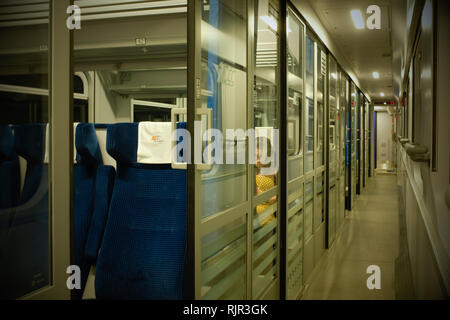 corridor on a train with separate compartments  on a railway passenger coach with one woman in a yellow dress. - Stock Photo