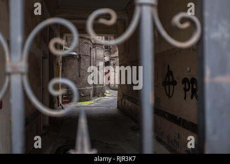 Alleyway leading into a courtyard in a ghetto tenement house in Warsaw seen through an iron gate - Stock Photo