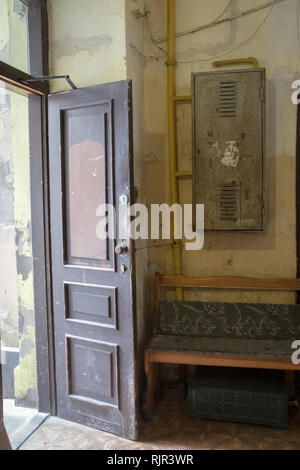 open wooden doorway with hallway into a tenement house with a bench - Stock Photo