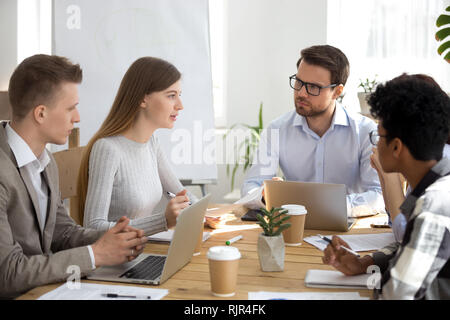 Diverse colleagues listen to coworker talking about new idea at meeting - Stock Photo