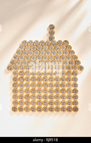 Collection of £1 Pound Coins in the Shape of a House - Stock Photo