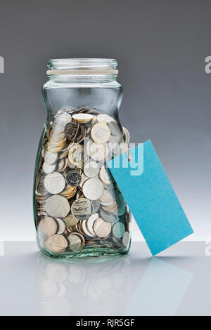 Glass Savings Jar with Pound Coins - Stock Photo