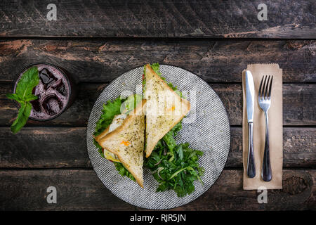 Sandwich with chicken and vegetables on a ceramic plate. Served with cutlery and fresh lemonade. Top view - Stock Photo