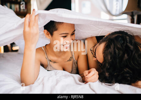 Happy couple under covers in bed - Stock Photo