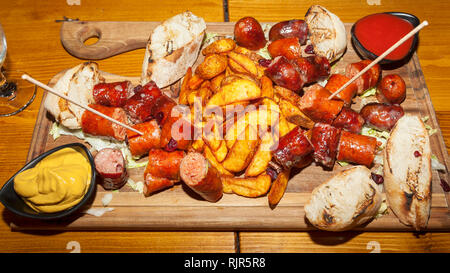 Pub food on wooden board - Sausages with cheese, roasted potato, mustard, ketchup and bread - Stock Photo