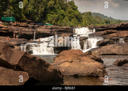 Cambodia, Koh Kong Province, Tatai, Waterfall, tourists on rocks amongst water flowing over falls in dry season - Stock Photo