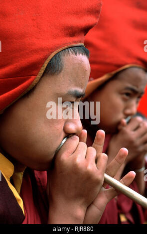Young monks playing ceremonial instruments during an annual festival at a monastery in Sikkim, India. - Stock Photo
