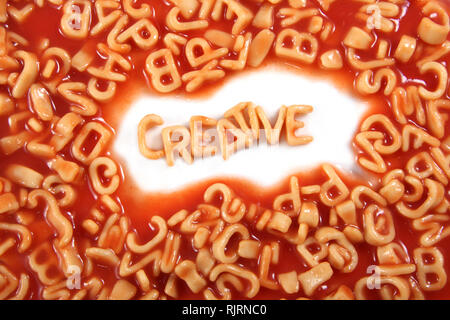 Creative written in spaghetti pasta letters surrounded with jumbled letters. - Stock Photo