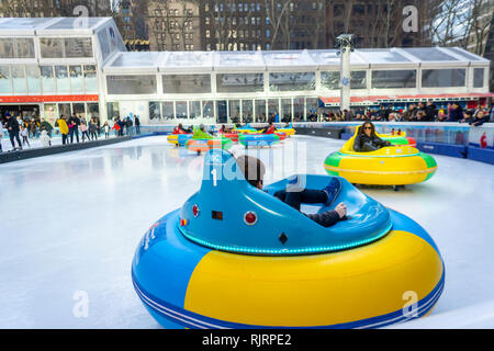 Visitors to the Winter Village ice skating rink at Bryant Park try out the new bumber cars attraction in New York on Sunday, February 3, 2019. (© Richard B. Levine) - Stock Photo