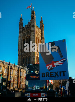 London, UK - Feb 7, 2019: Anti-Brexit placard outside, Westminster, London, UK depicting Brexit as shooting the UK in the foot with double-decker bus painted with Union Jack colours in background Credit: Alexandre Rotenberg/Alamy Live News - Stock Photo