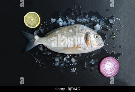 Fresh Raw Fish isolated on dark vintage background with ice from top view - Stock Photo