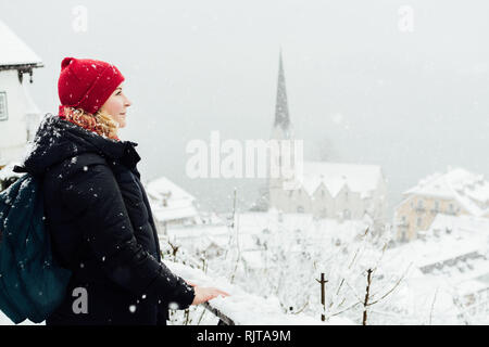 Woman in red hat enjoying the view over Hallstatt old town during snow storm, Austria. - Stock Photo