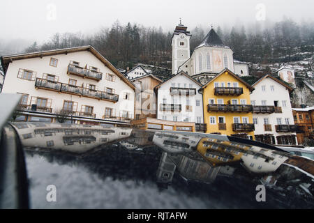 HALLSTATT, AUSTRIA - JANUARY 2019: reflection of old town houses and forest in the car roof - Stock Photo
