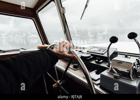 HALLSTATT, AUSTRIA - JANUARY 2019: view over Hallstatt town and Alps mountains from ferry boat captain's cabin. Hand on the steering wheel. - Stock Photo